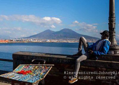 Migrante assorto davanti al Vesuvio